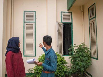 surveyor menjelaskan hasil survey anti rayap terhadap kayu kusen kepada pelanggan